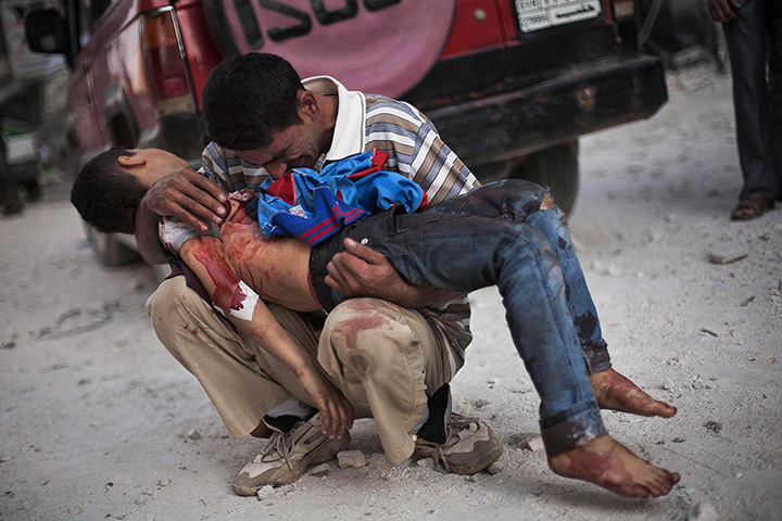 A Syrian man cries while holding the body of his son